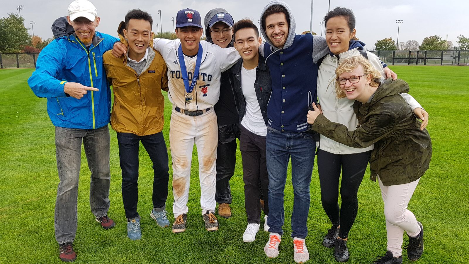 A smiling group of people stands around a baseball player.