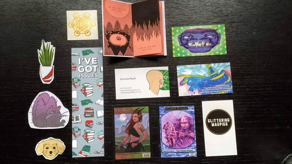 aligned on a table-top are a collection of colorful illustrated business cards, stickers, and a small booklet