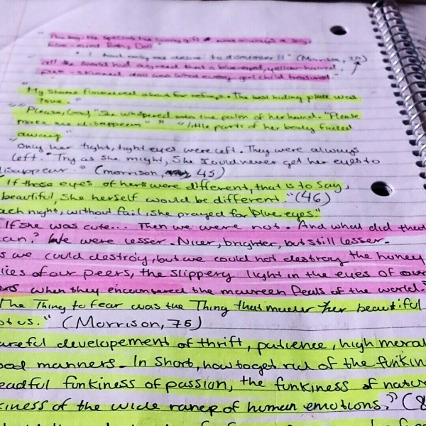 a notebook page littered in writing and highlighted in many different colors