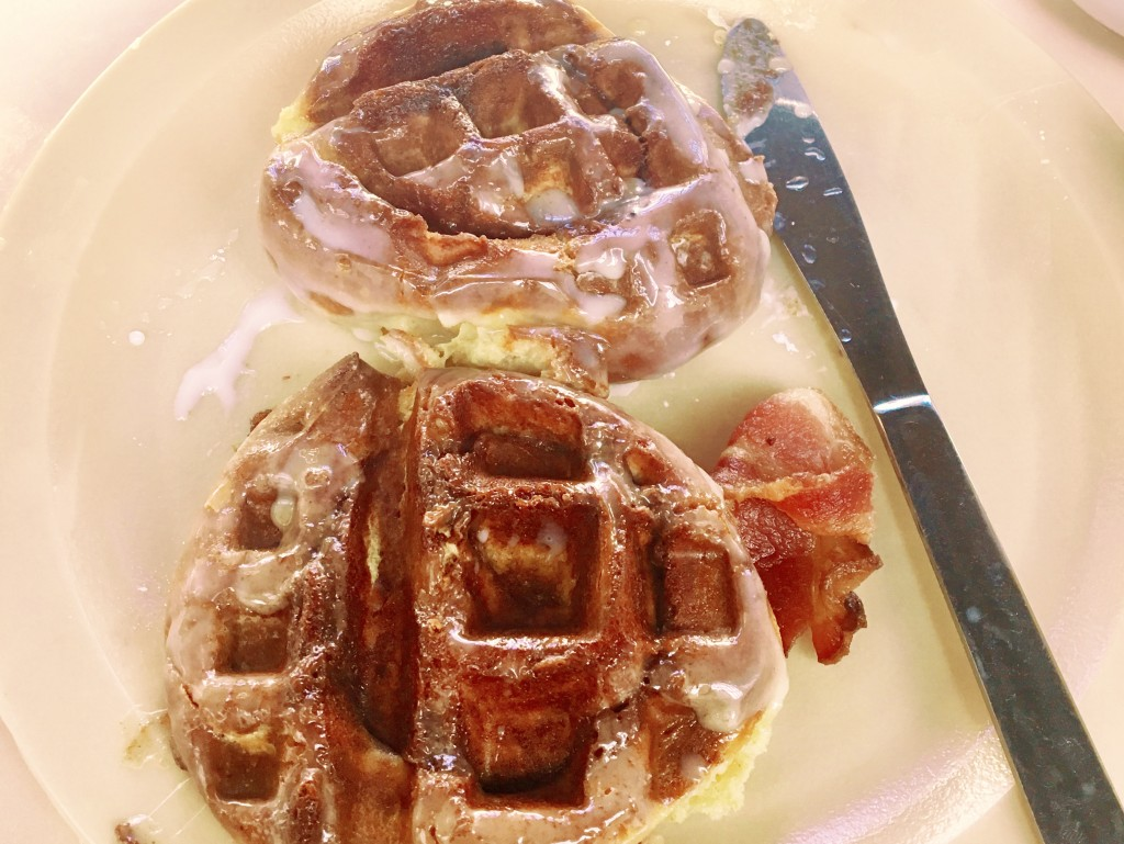 A photo of two cinnamon buns on a plate after being put in a waffle press.