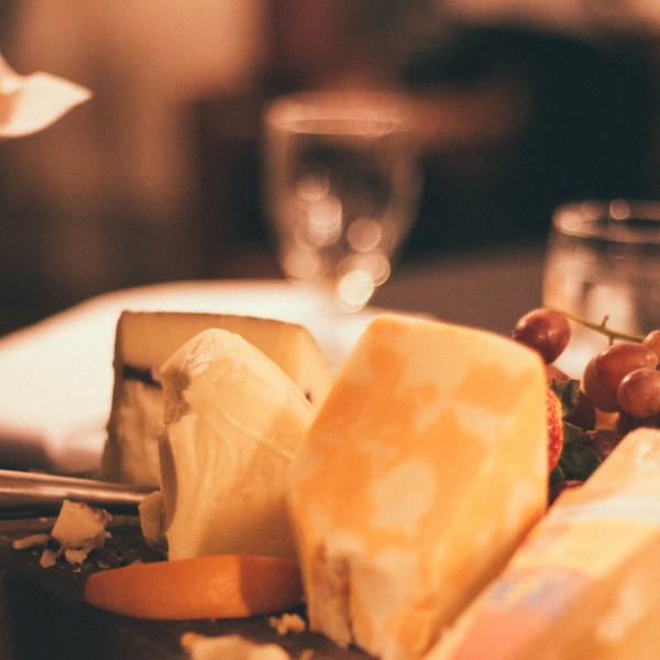 A photo of several blocks of different kinds of cheese on a platter.