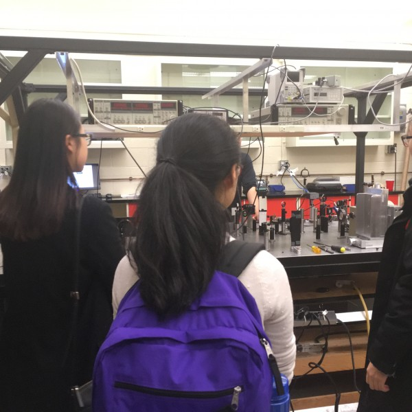 Photograph of 3 individuals watching a presentation in a physics lab