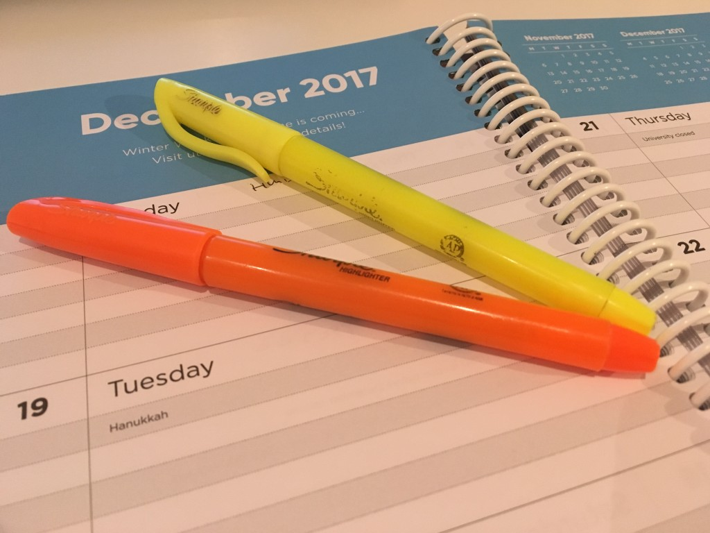 Photo of agenda page with 1 orange highlighter, 1 yellow highlighter lying on top