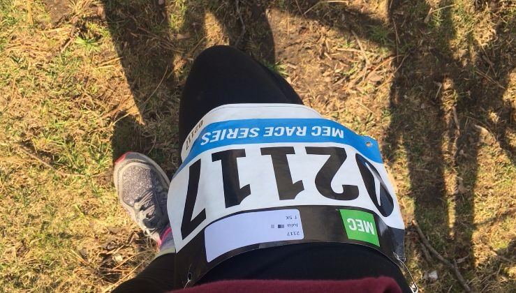 A runner displays a numbered bib on her leg.