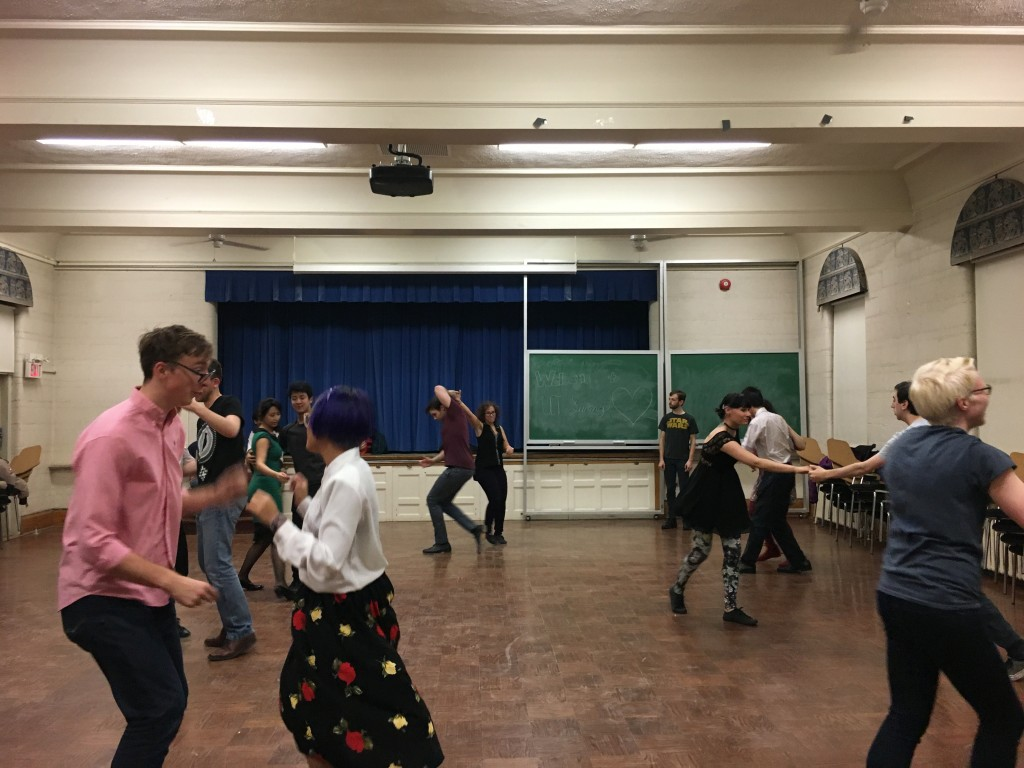 a group of people dance in pairs.