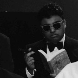 Picture of Avneet in a tuxedo and sunglasses reading The Catcher in the Rye.