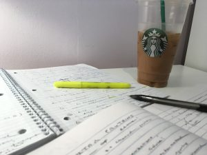 Photograph of desk with handwritten study notes and Starbucks iced coffee