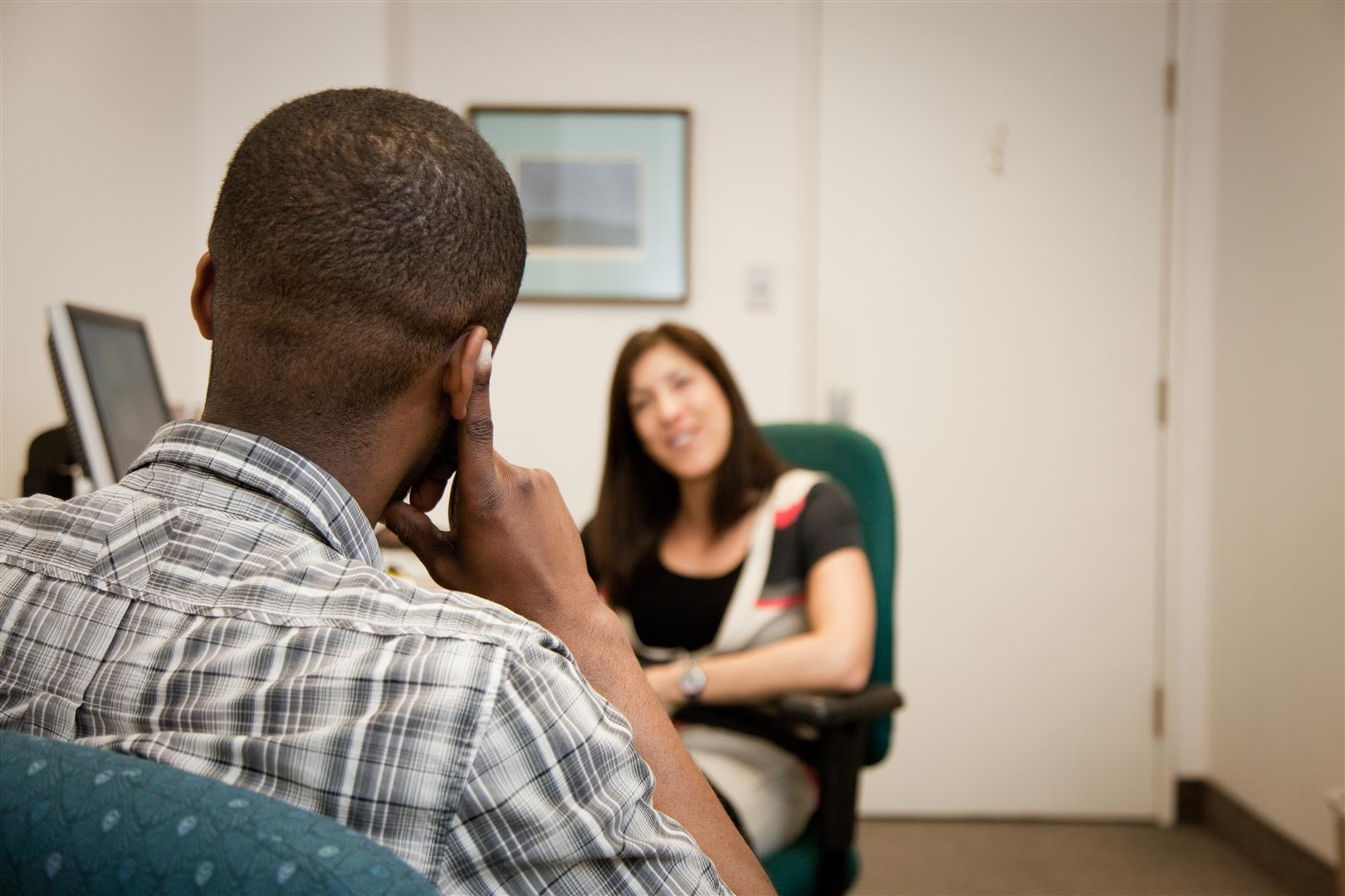 A man and a woman sitting face to face engaged in a conversation.