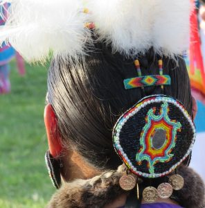 Indigenous woman wearing beading and feathers