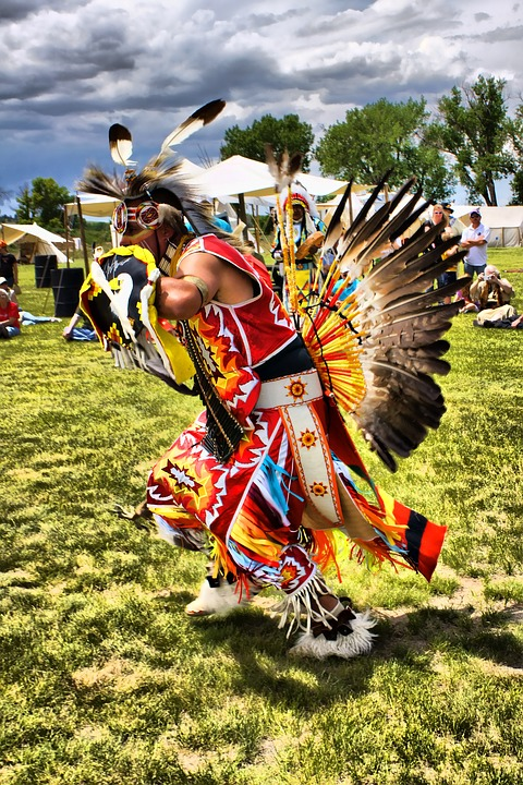 A dancer in regalia dancing at a pow wow