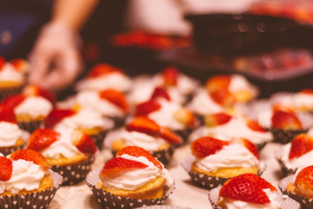 A photo of tarts covered in whipped cream and fresh strawberries.