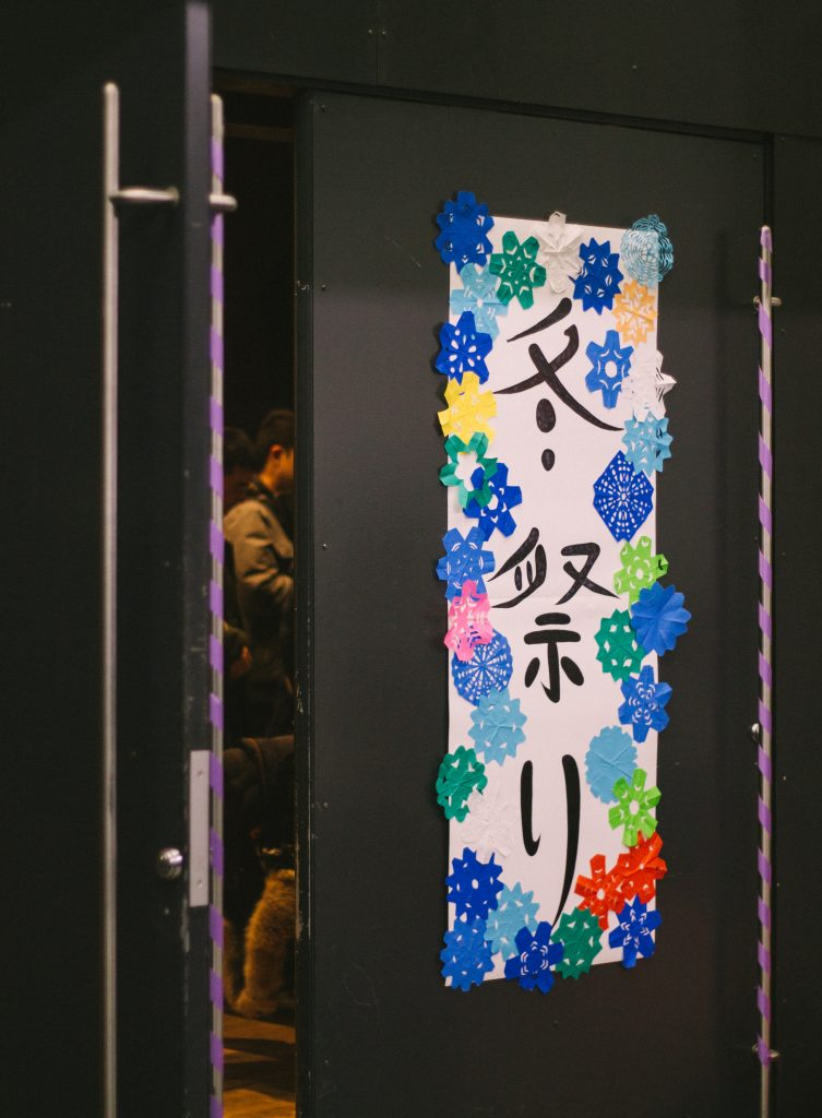 A poster that says Winter Festival in Japanese. Paper flowers adorn the poster.