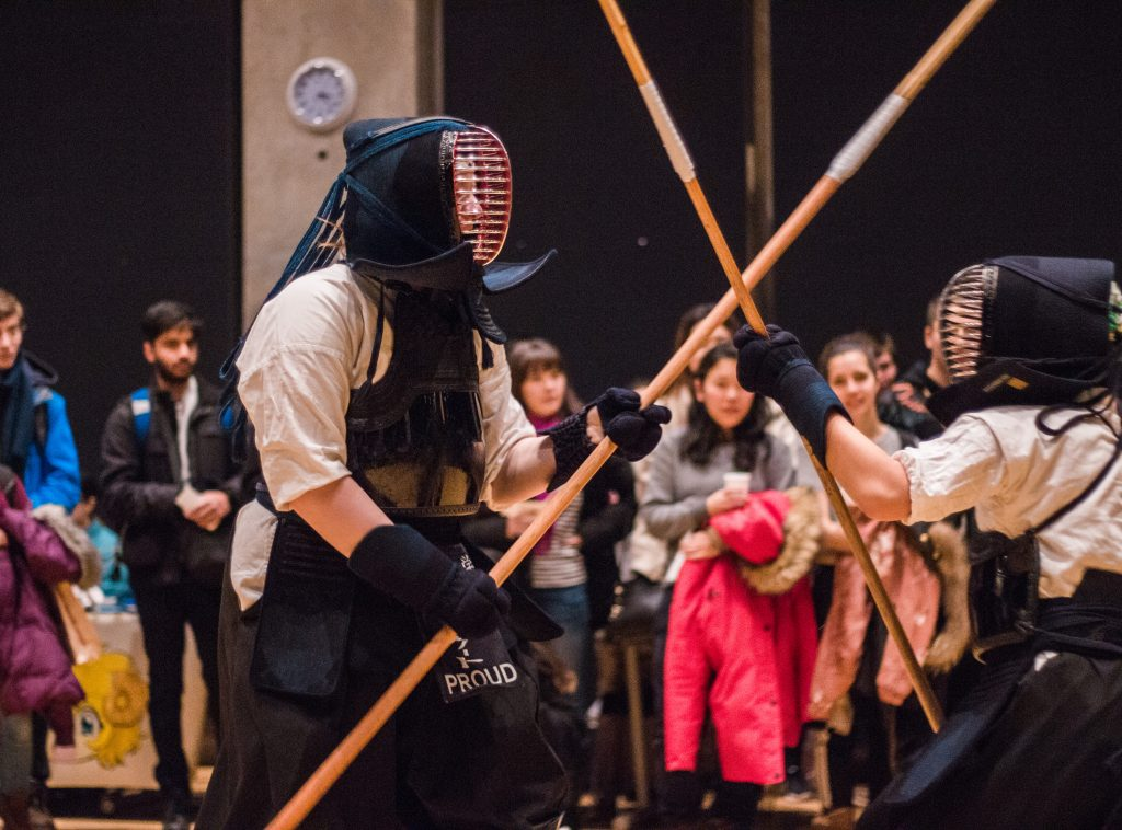A photo of a naginata fight, surrounded by spectators.