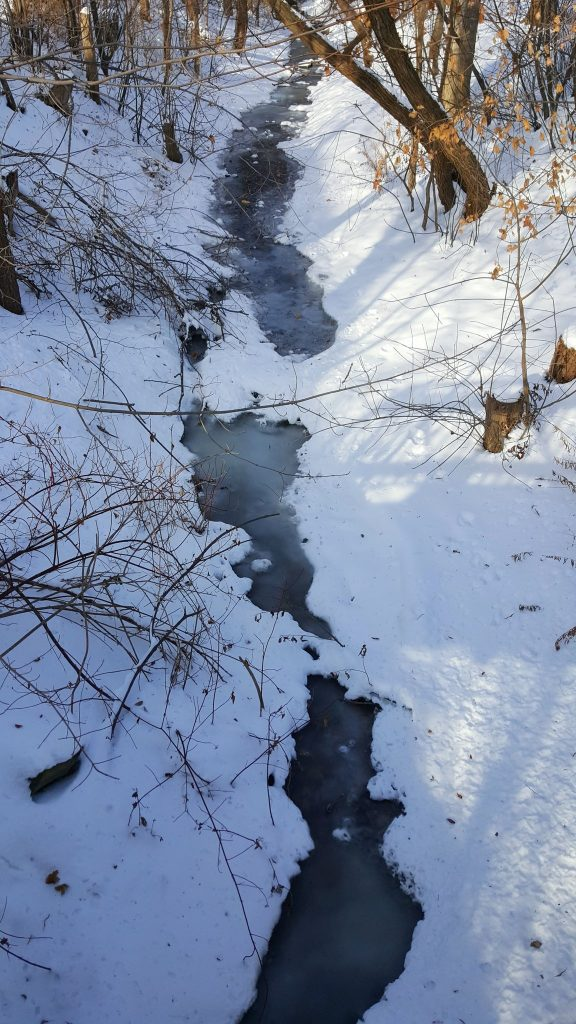 A small creek, frozen over and banked by snow piles