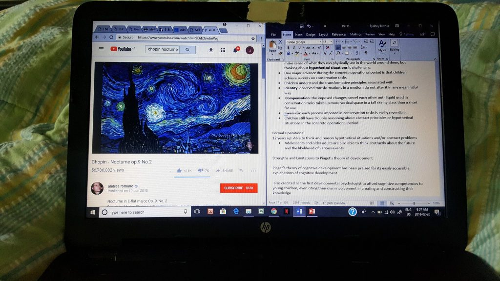 a photo of a laptop screen, half taken up by a youtube video of Chopin's Nocturne, and half taken up by a word document of psychology terms