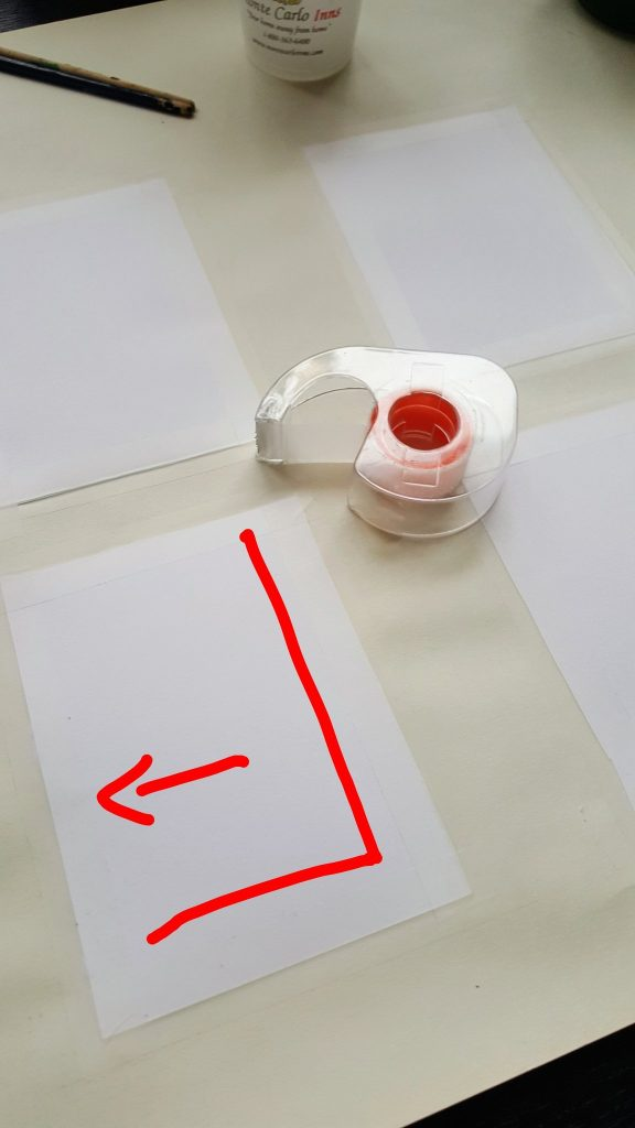 A rectangle of white paper taped down to a large beige surface