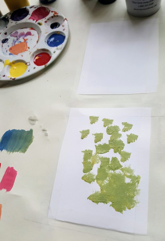 another rectangular paper panel, littered in green splotches of paint