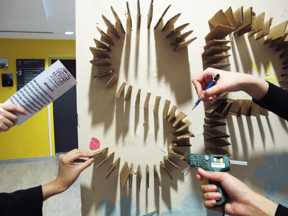 An artistic perspective photo of the different roles and elements required to build the flower mural; many hands each holding an element such as a glue gun, pencil, cardboard and a brochure to fan the glue