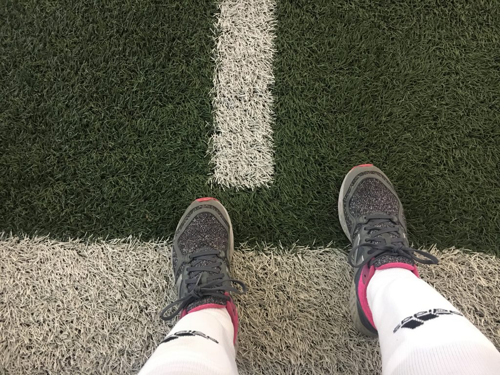 Some feet wearing running shoes, shin guards, and soccer socks on a green field.