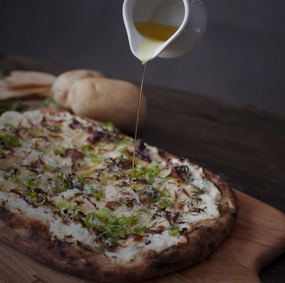 white truffle oil being slowly drizzled onto a square pizza with thick crust