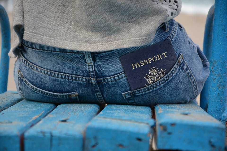 Photo of someone sitting with passport sticking out of pants pocket