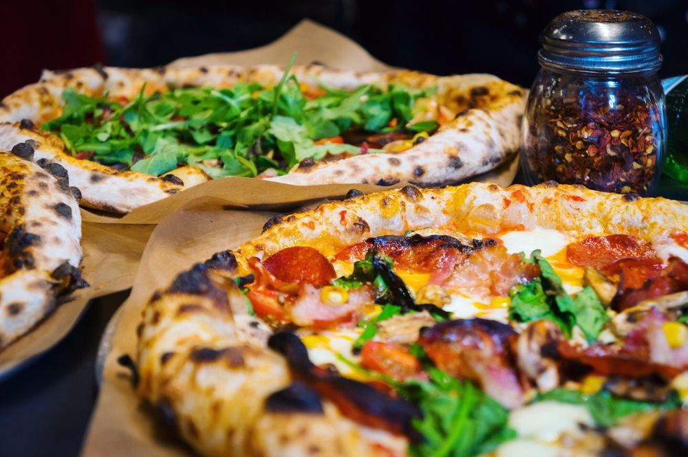 two pizzas, one with cheese and meat and one with arugula