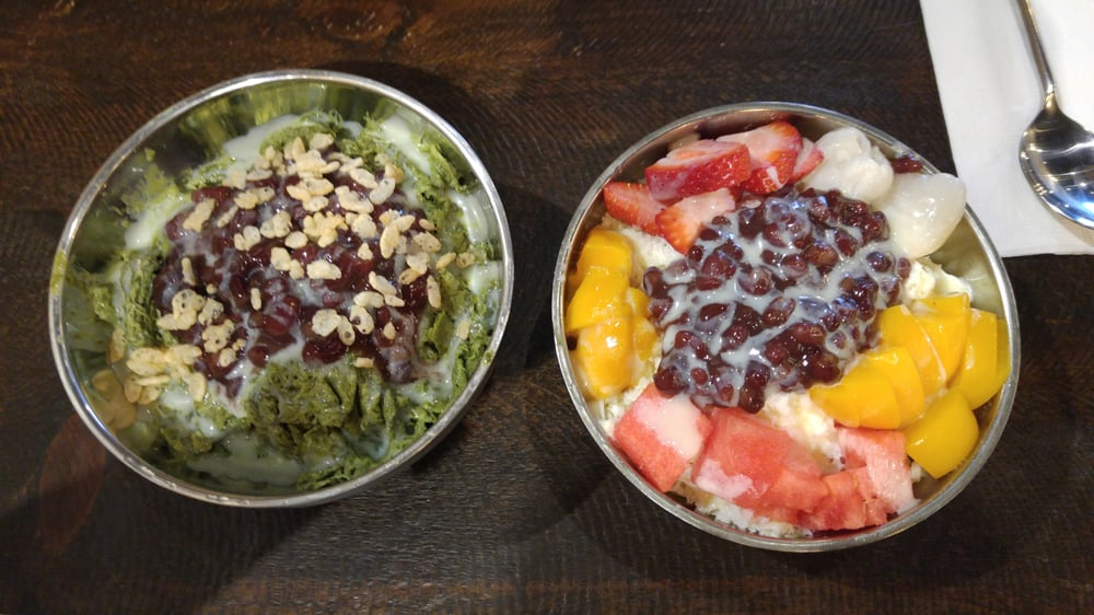 two bowls containing desert foods, with a variety of fruit and nuts atop warm sticky rice