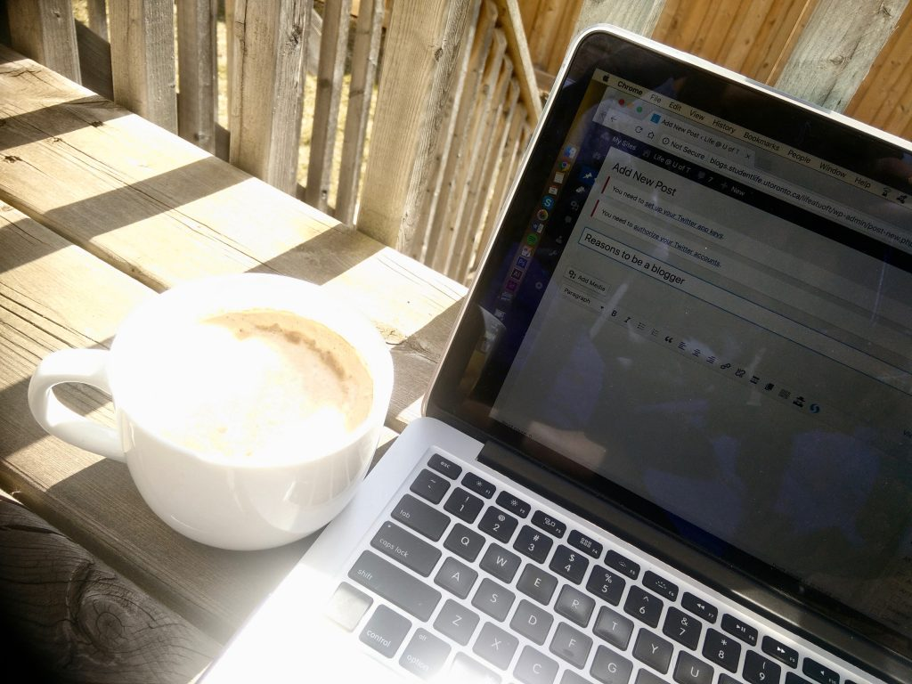 picture of my laptop and big cup of coffee on my backyard deck