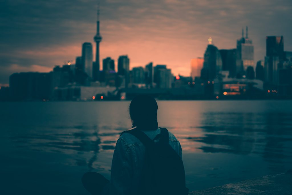 As night falls, a person stands and looks at the Toronto skyline.