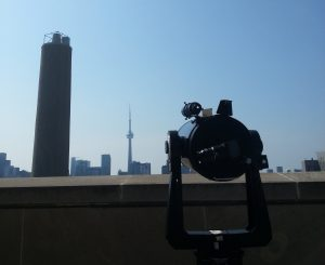Telescope on roof pointing at CN Tower