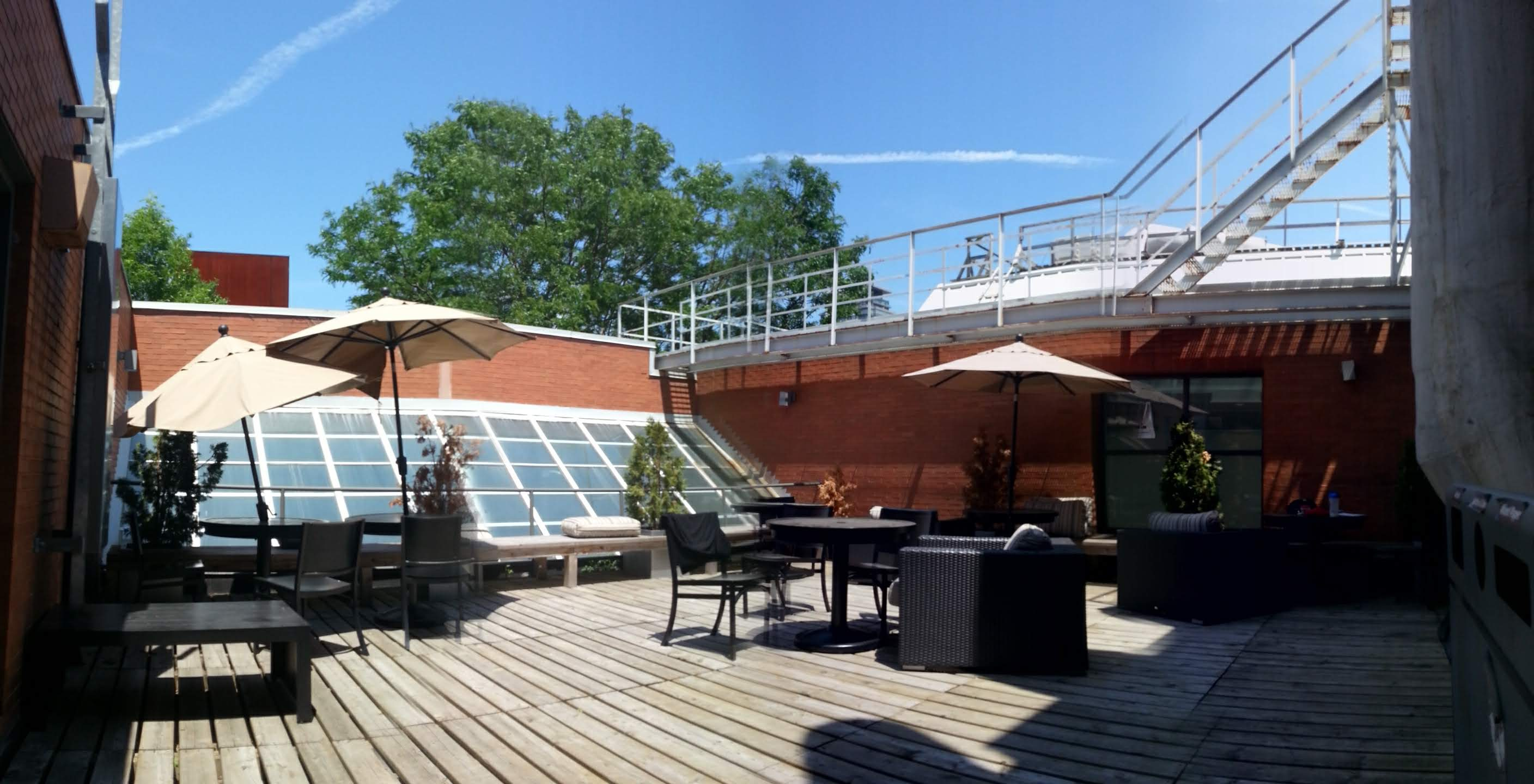 Terrace with patio furniture and trees at Innis College