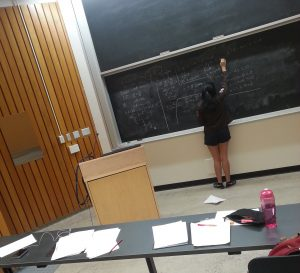 girl writing on blackboard in lecture hall