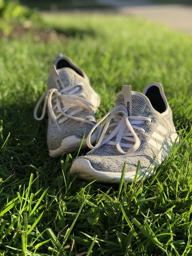white and grey running shoes laying on grass.