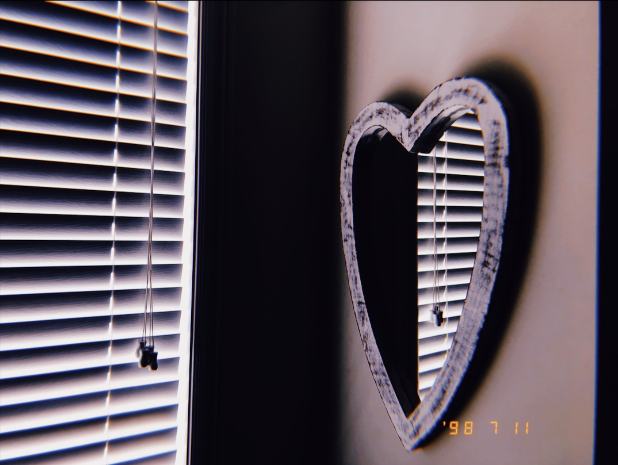 image of a heart shaped mirror handing on a wall by the corner. The reflection shows closed blinds that let the soft glow of the morning light through.