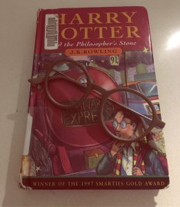 Harry Potter and the Philosopher's Stone by J.K. Rowling front cover with round framed glasses on top