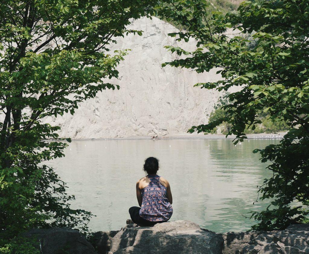 girl sitting on rock facing lake