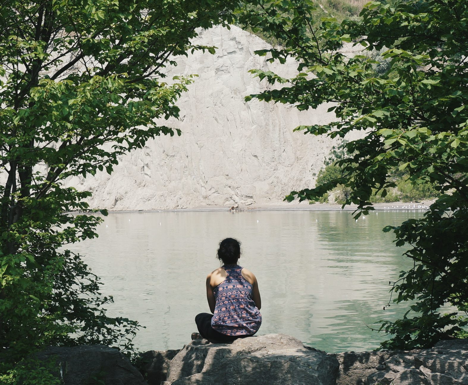 girl sitting on rock facing lake
