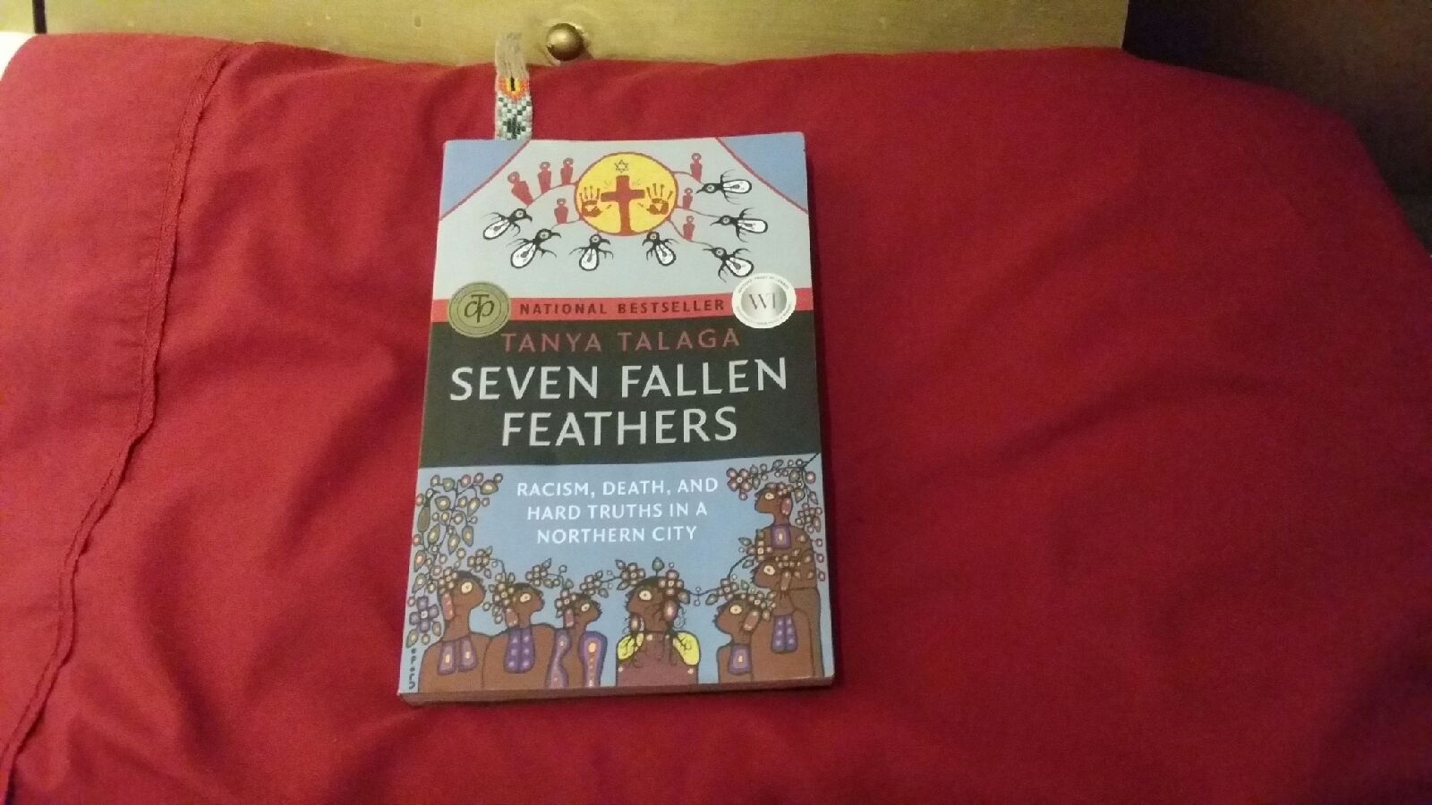 A picture of Seven Fallen Feathers, a book I need to complete for one of my classes. Caption: Maybe I wouldn't have fallen asleep if I didn't read in bed?