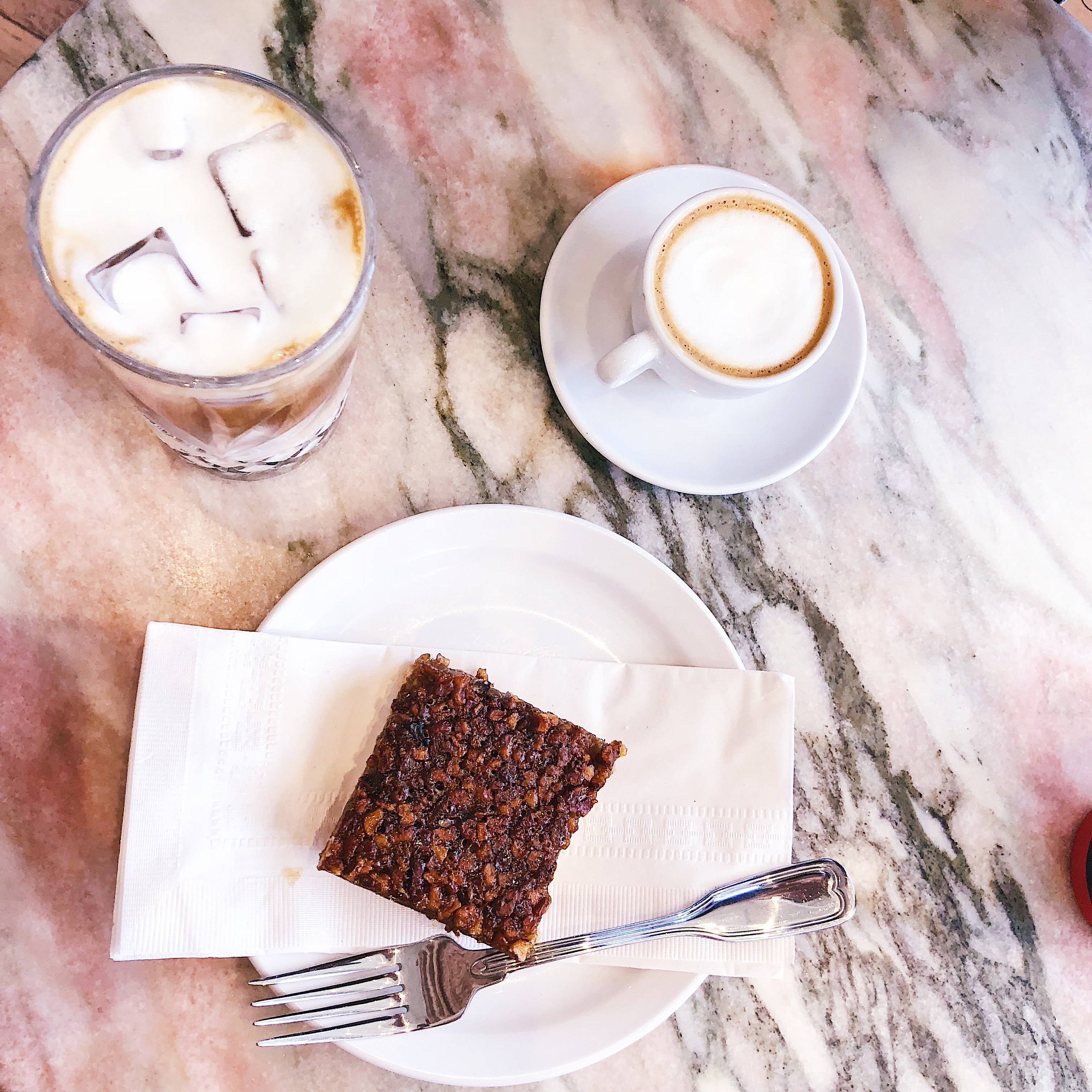 Two coffees with pecan pie on a marble table
