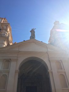 Photograph: upwards shot of center section of Spanish colonial style church, top of doorway and statue of jesus carrying a cross on top of roof, radiating sunlight from right side of image. Church is pale tan/off white in color, blue sky background