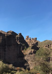 Photograph: unusual mountainous rock formations tan-ish in color, left hand side in shadow, blue sky background, tree in lower righthand corner foreground,