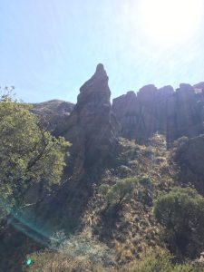photograph: upwards angle of mountainous rock formations, trees in foreground, bright rays of sunlight from upper righthand corner