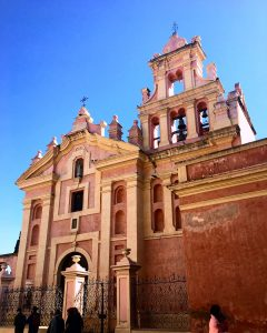 photograph: Spanish colonial style church facade, peachy pink in color, background is blue sky