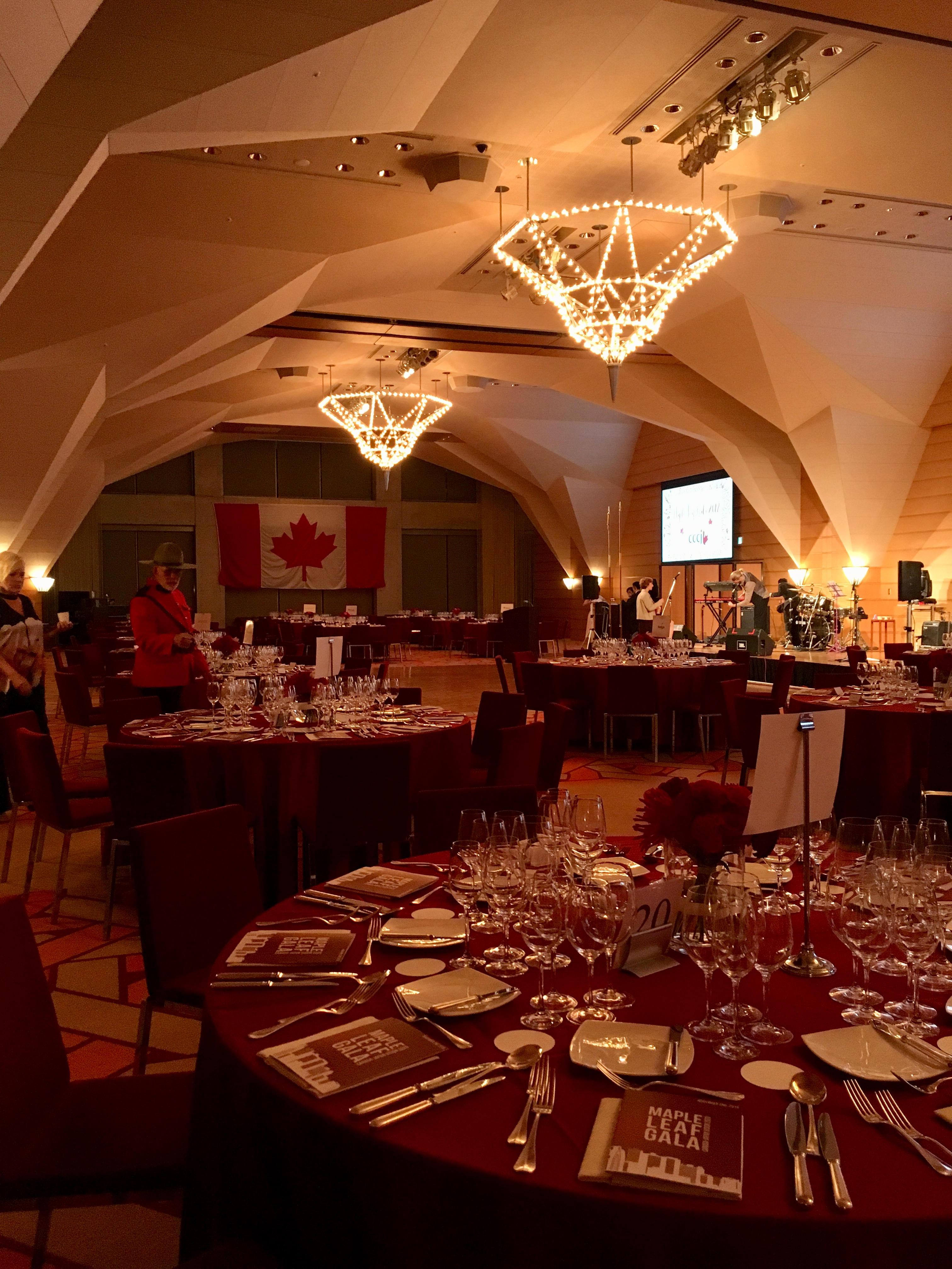 A large dining room with table settings and a Canadian flag in the background.