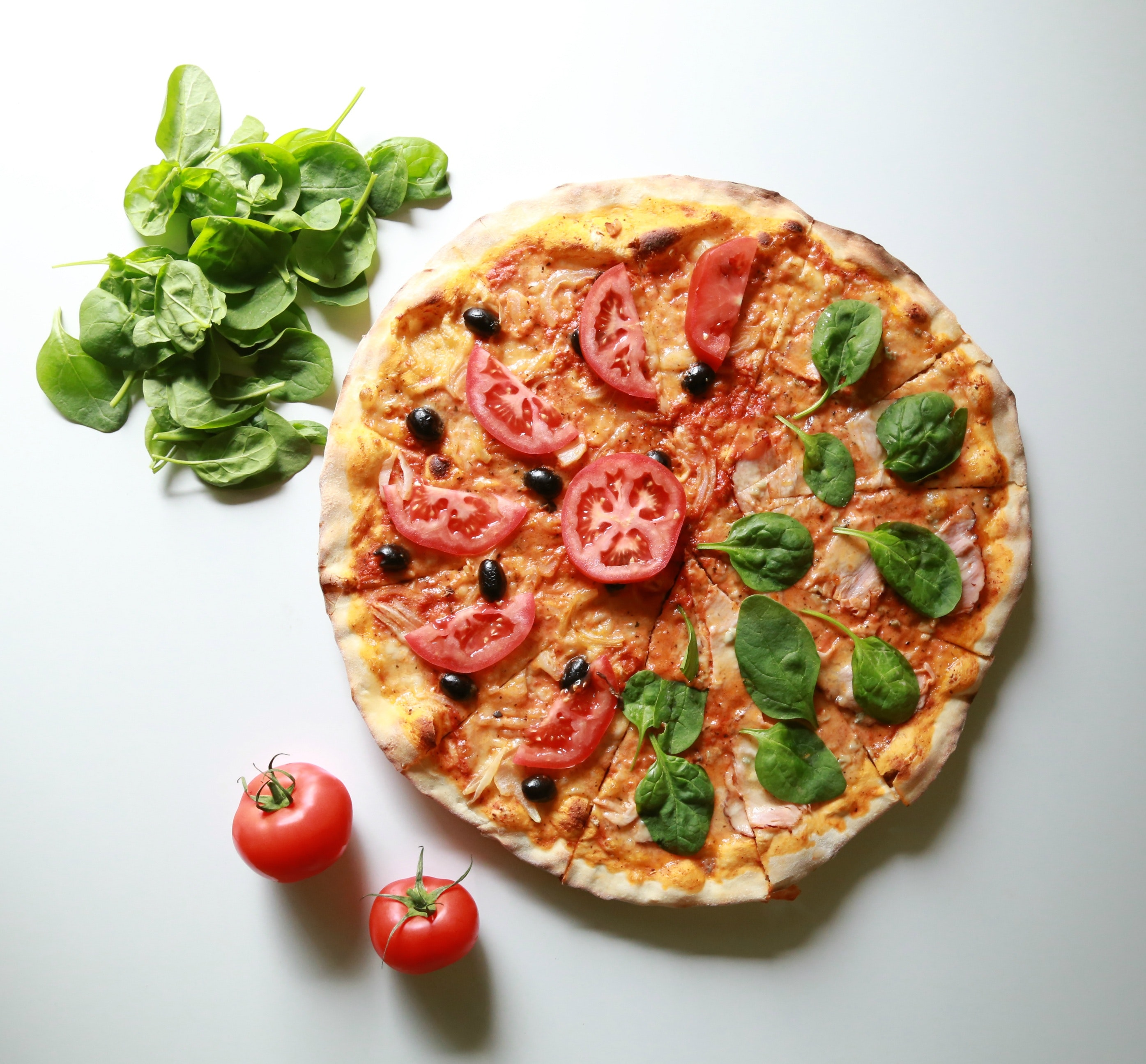 A stock photo of an arugula-tomato pizza. Caption: Believe it or not, but you can actually get tired of eating pizzas