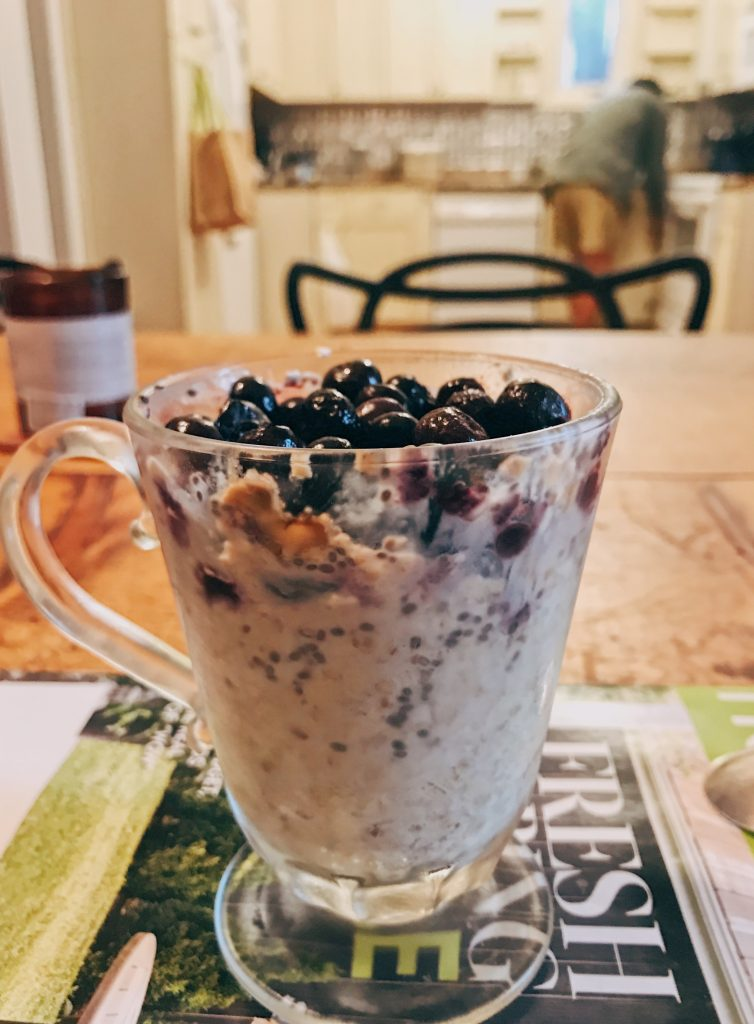 Oats topped with blueberries in a glass cup.