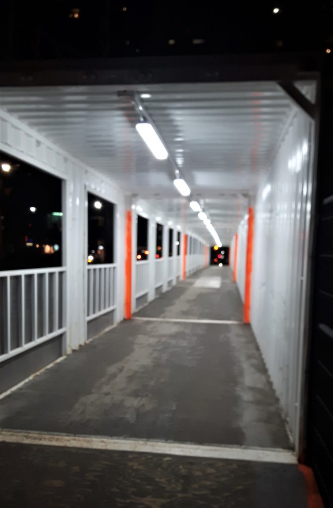A photo of a long, empty walkway outside.