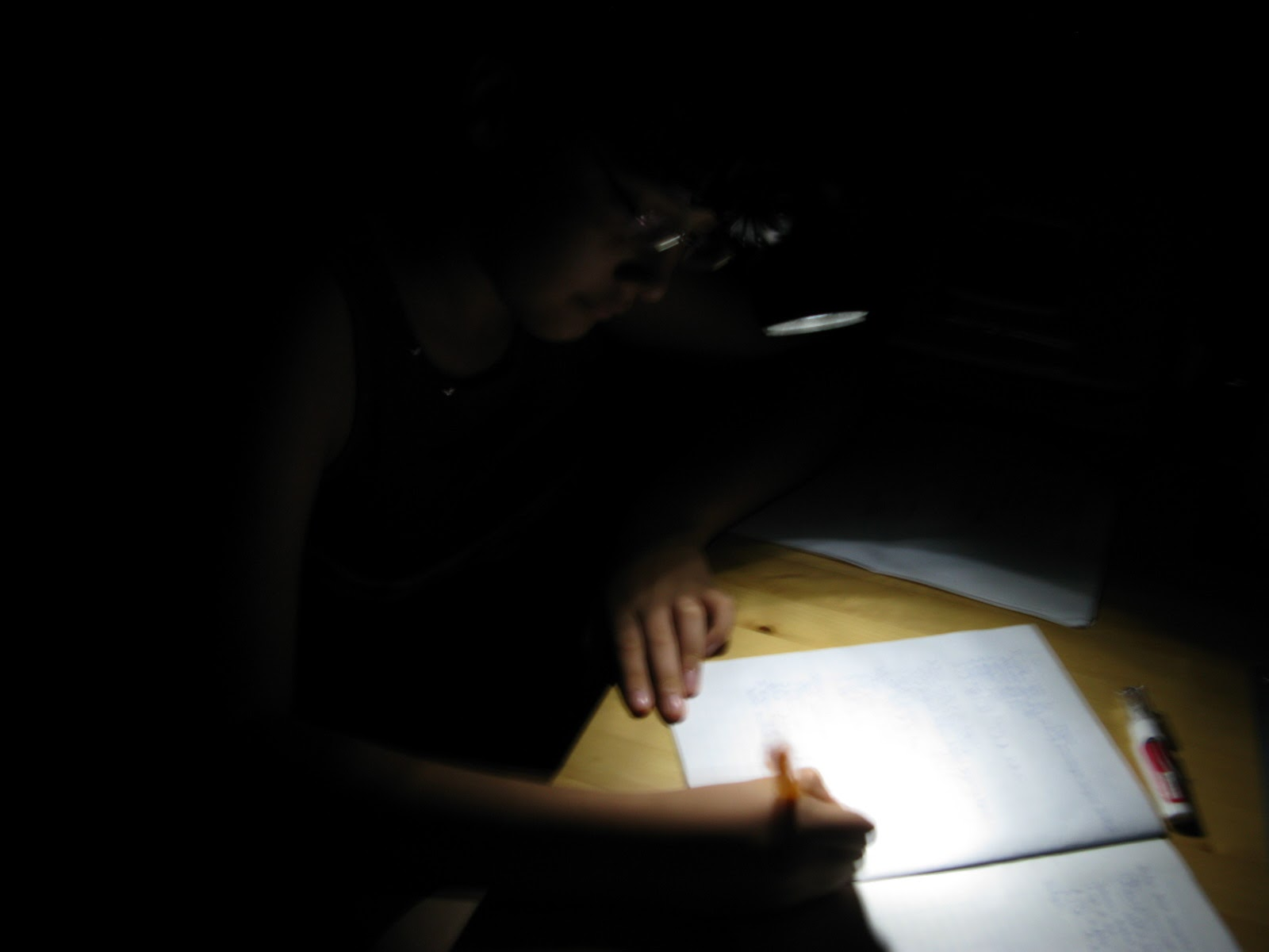 girl working on homework using head lamp