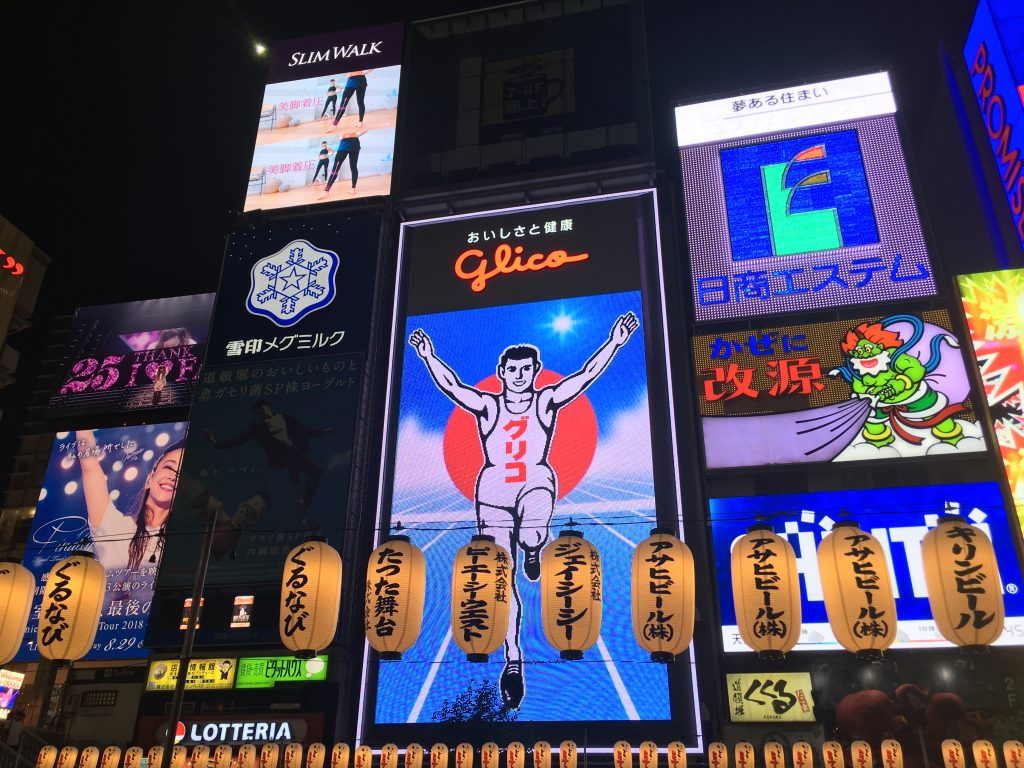 The Glico Running Man is a neon sign, holding his arms in the air in victory.