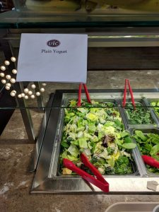 "A photo taken in the dining hall, the salad mix is labeled ""Plain Yogurt""."